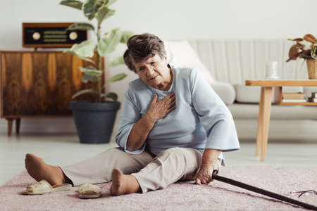 Disabled elder lady sitting on the floor with a walking stick and holding her chest after falling down