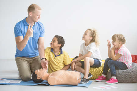 Paramedic showing two fingers to group of children during first aid training with manikin on the floor Stock Photo
