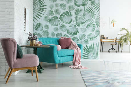 Bright flat with white brick wall and monstera leaves wallpaper in botanic living room Stockfoto