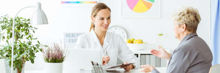 Smiling nutritionist making notes during an appointment with a client in the office 版權商用圖片 - 97009895
