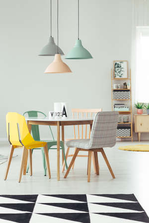 Lámpara de durazno, menta y gris sobre mesa redonda y silla amarilla en el interior del comedor con alfombra blanca y negra Foto de archivo