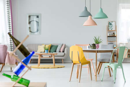 Mint and yellow chair at table with kettle under pastel lamps in spacious flat interior with cushions on sofa near yellow round carpet
