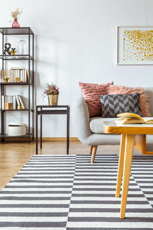 Book on wooden table and heather in gold pot on black stool in living room interior with pink and grey cushions on sofa against a wall with yellow painting