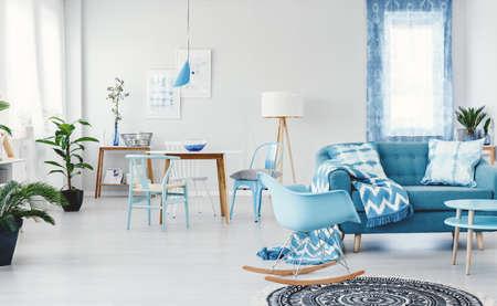 Blauer Schaukelstuhl nahe bei Sofa mit kopierter Decke im geräumigen Wohnzimmerinnenraum mit Anlagen, Lampen und Tabellen Standard-Bild - 97678284