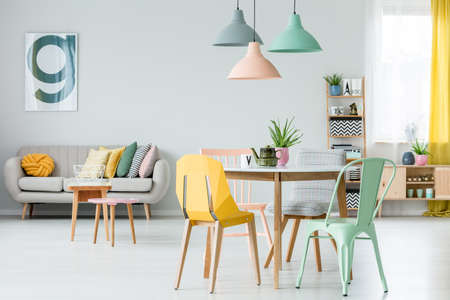 modern colorful chairs at dining table under pastel lamps in stockmodern colorful chairs at dining table under pastel lamps in living room interior with pillows on