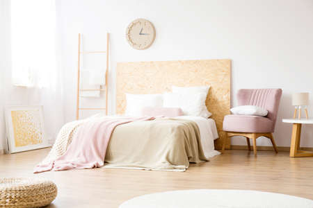 Pink armchair standing next to a bed with pink and beige blankets in simple bedroom