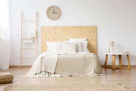 Beige, knit blanket on white bed with wooden bedhead next to a small table with lamp in minimalistic bedroom Фото со стока