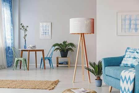 ダイニングテーブルと椅子付きの多機能リビングルームのインテリアにパターン枕付きの青いソファの隣に木製のランプとヤシ