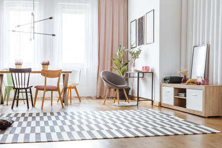 Grey chair at table with pink vases and patterned carpet in cozy living room interior with dining table and wooden chairs