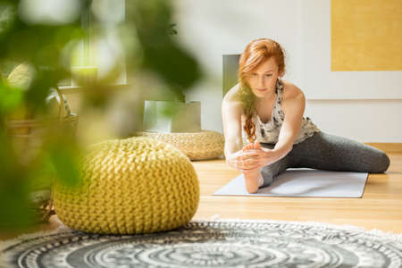 Active woman exercising on the floor at her home with yellow decorations Standard-Bild