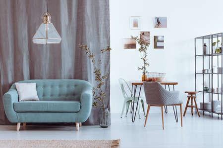 Espaço aberto, sala de estar e jantar com galeria de fotos penduradas em uma parede branca acima da mesa de madeira