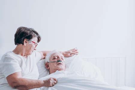 白い病院のベッドに横たわっている彼女の病気の夫を慰める高齢の女性 写真素材