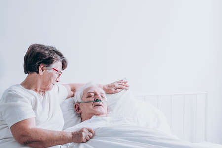 Elderly lady comforting her ill husband lying in a white hospital bed