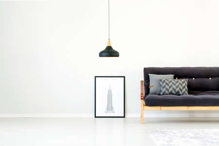 Black lamp and poster next to sofa with grey cushions in monochromatic living room interior with copy space 版權商用圖片
