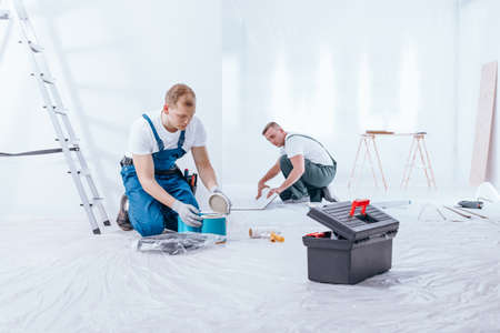 Men preparing interior to renovation with protective film, black toolbox and rollers on the floor Stock Photo