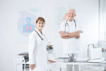 Two doctors in uniforms standing at the office and talking about a patient