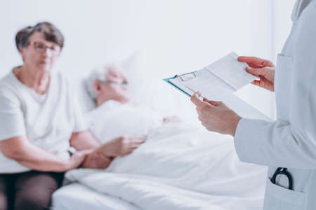 Doctor reading a medical report to a patient and his wife in a hospital