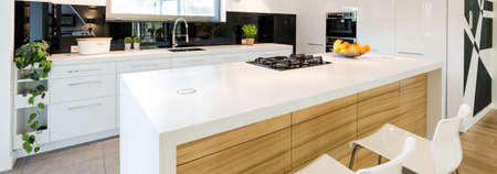 Cozy spacious kitchen in white and black. In the middle wooden island with white wheat Фото со стока