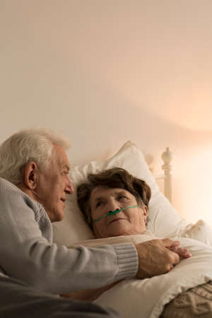 Elderly man taking care of his sickly wife who is lying in bed being lit by a dim lamp light Stock Photo