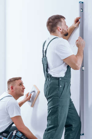 Handyman using bubble level on white wall while his colleague cleaning the wall Stock Photo