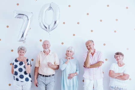 Senior couple celebrating their birthday together with friends and family at a party