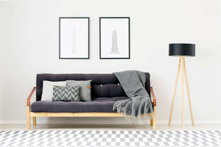 Posters above black settee with pillows and grey blanket next to wooden lamp in living room interior with patterned carpet