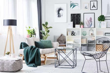 テーブルの近くに黒い椅子、プーフと壁に木製のランプとポスターと明るいリビングルームのインテリアに緑のクッションとセッテ