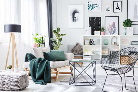 Black chair near a table, pouf and settee with green cushions in bright living room interior with wooden lamp and posters on the wall Stockfoto