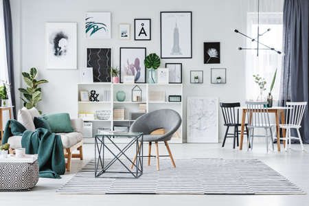 Grey chair on patterned carpet near sofa in spacious living room interior with gallery of posters and dining table