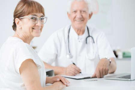 Senior female patient with glasses smiling during periodic medical examination Stock Photo