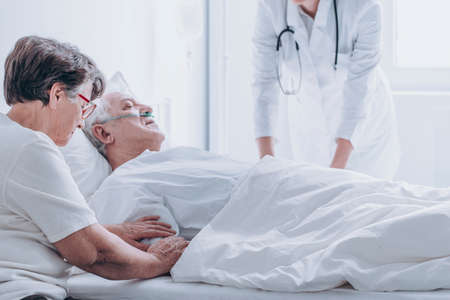 Doctor pronouncing death of an elderly patient in a presence of his spouse Stock Photo