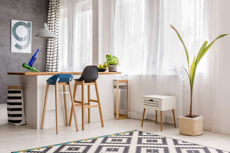 Simple dining area with tall plant, wooden barstool, white kitchen island and poster on gray wall