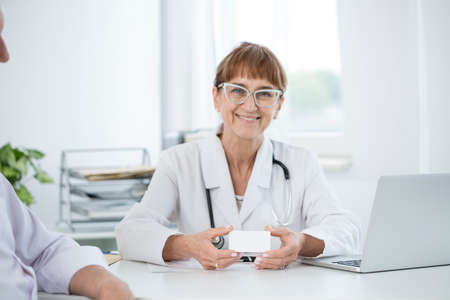 Elder lady doctor with glasses sitting by the desk at her office and holding a business card