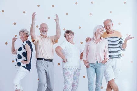 Elderly friends dancing and talking at a casual new years party with gold dots wallpaper