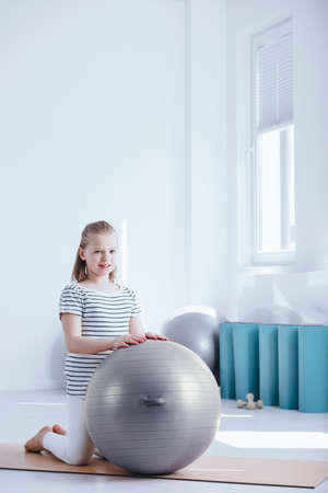 Young kid waiting for her physiotherapist with grey exercise ball at the gym Stock Photo