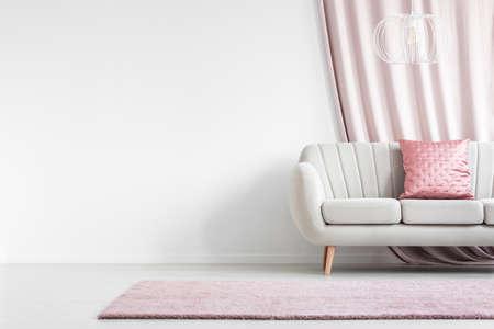 빈 벽과 밝은 거실 인테리어에 새틴 베개와 흰 소파의 앞에 핑크 깔개