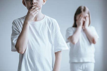 口を覆う白いシャツを着た少年と背景に立つ小さな女の子 写真素材 - 94220694
