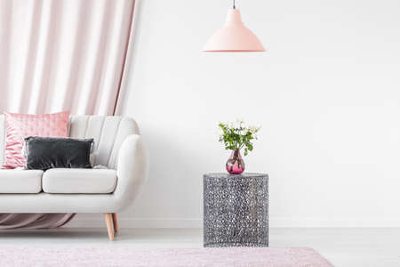 Metal table next to beige sofa with pink and gray pillow in bright interior of living room Stock Photo