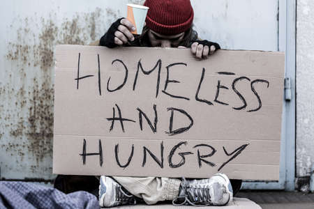 Tramp sitting on the street with a cup for money and holding a sign with text Homeless and hungry