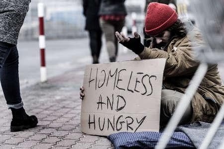 Vuile en hongerige dakloze man die bedelt in een drukke straat in de stad