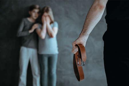 Foto de niños asustados en el fondo borroso y el hombre que sostiene un cinturón de cuero en primer plano