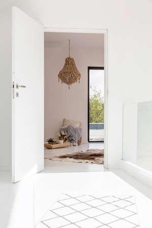 Salão branco com entrada para sala étnica com lustre decorativo e peles no chão Foto de archivo - 94417297