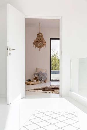 White hall with entrance to ethnic room with decorative chandelier and fur on floor