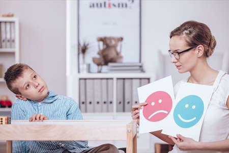 良い行動と悪い行動の自閉症の子供を教える赤と青のアイコンのポスターを持つカウンセラー