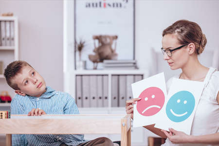 Counselor with posters of red and blue icons teaching autistic kid of good and bad behaviors 免版税图像