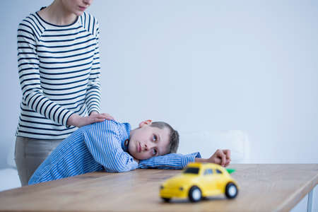 In the background autistic child with apathy lying on a table and mother supporting him Stock Photo