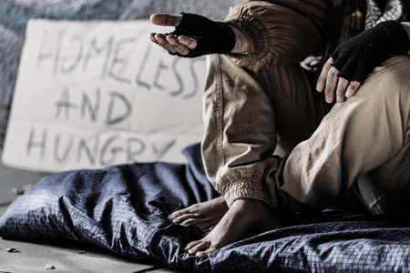 Close-up of dirty and barefoot street person sitting on a blanket and begging Stock Photo