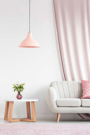 Bright living room interior with beige sofa, peach lamp, wooden table and roses in pink vase