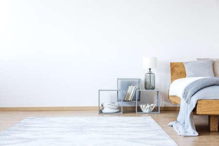 모직 담요, 선반 및 설 흰색 카펫 침대와 빈 흰색 침실 인테리어