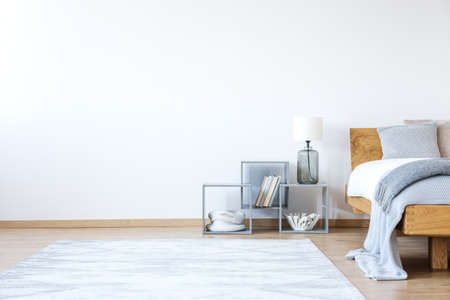 Empty white bedroom interior with bed with woolen blanket, shelves and snowy white carpet